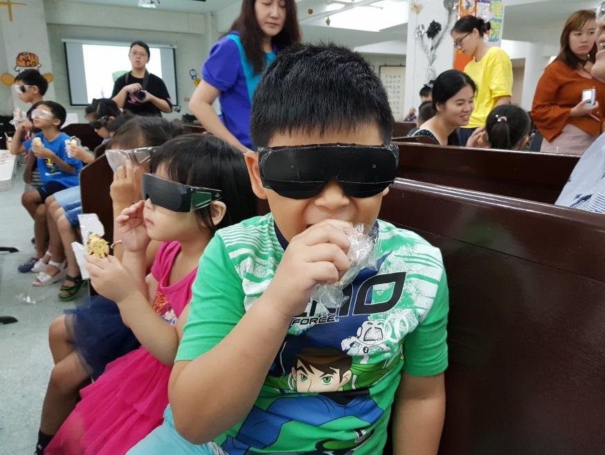 戴著視覺模擬眼鏡讓小朋友以觸摸的方式感覺點心位置並開心品嚐