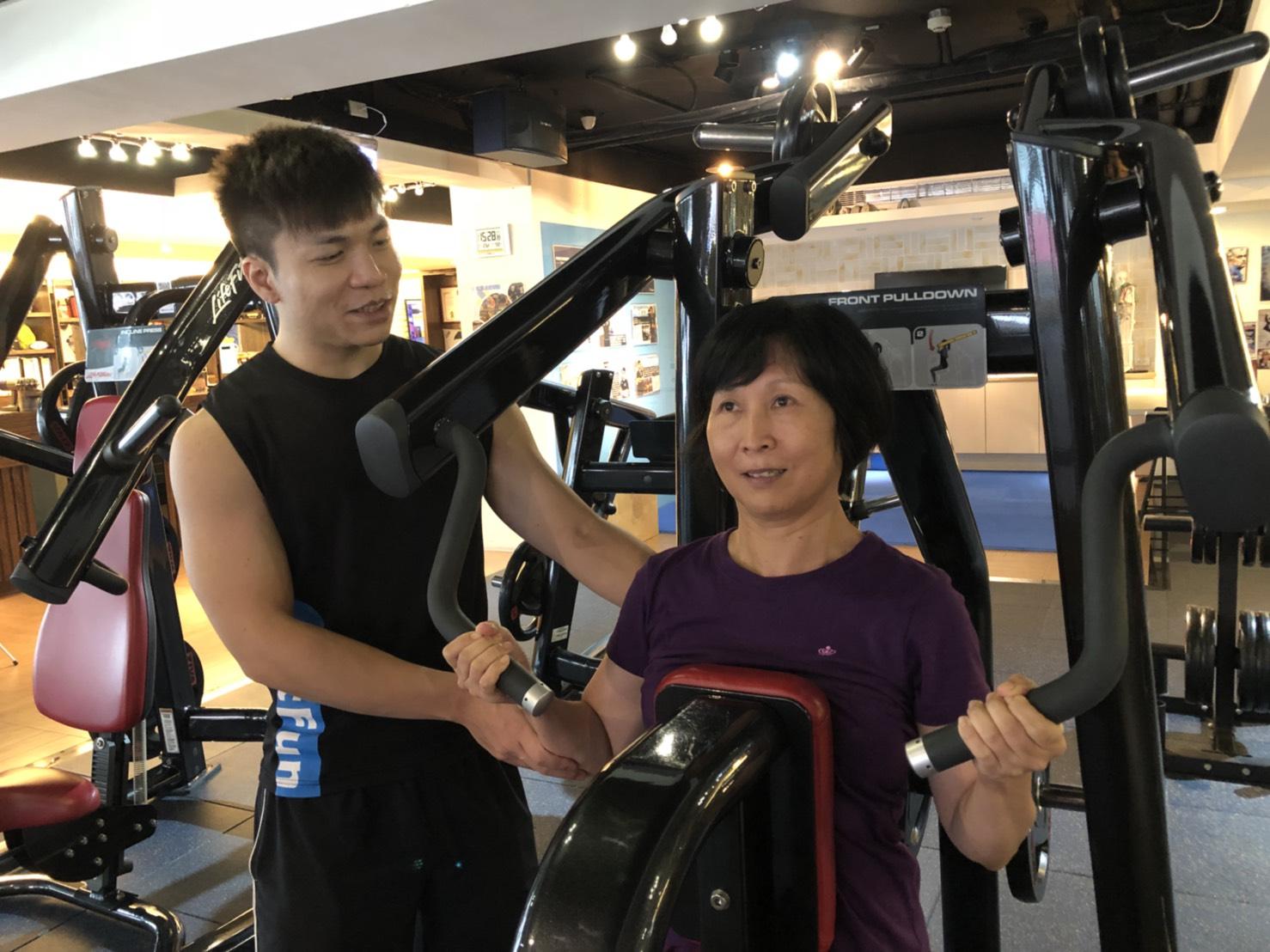 健身房課程教練協助小英操作器材