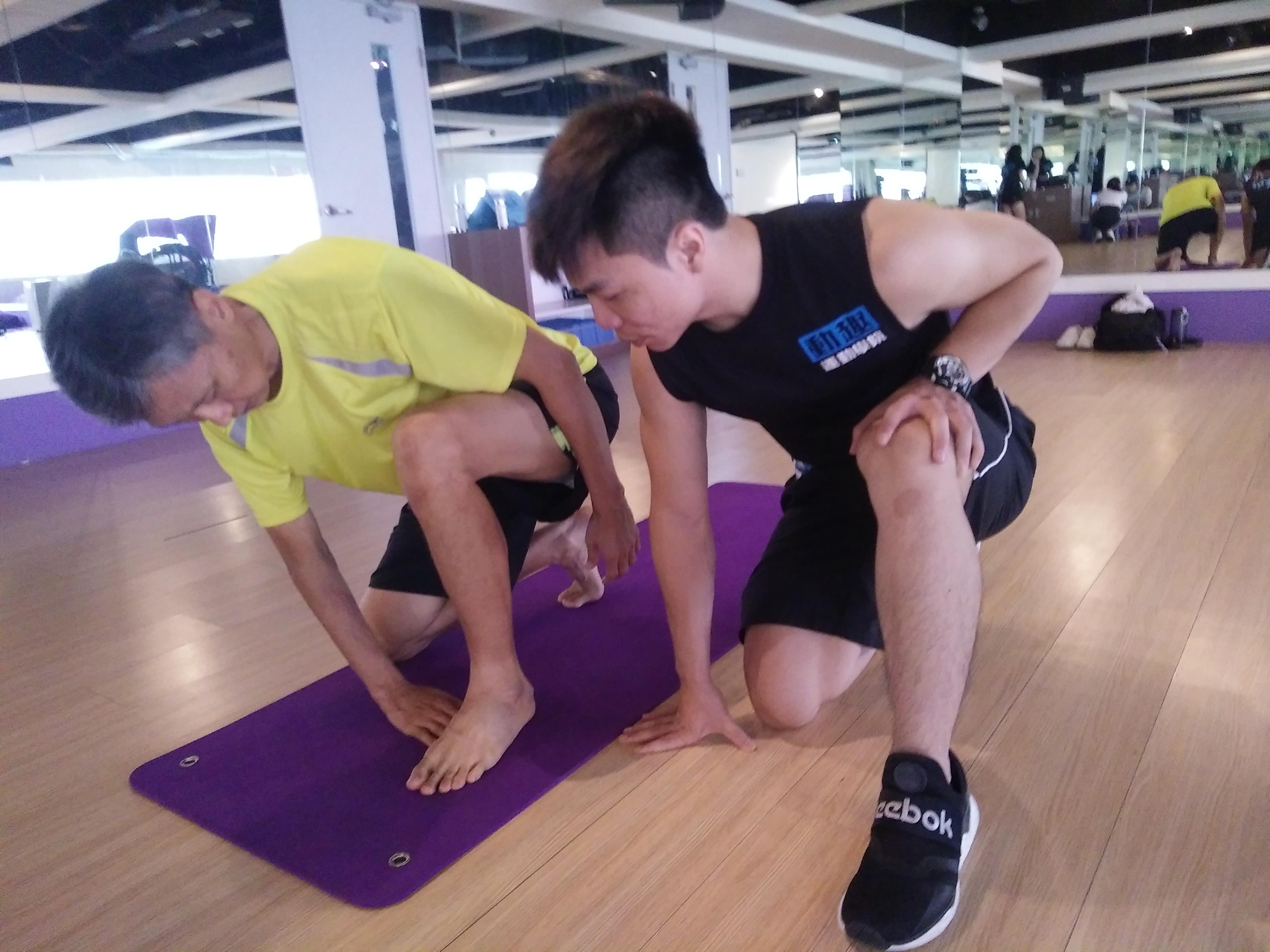 在體適能教練的協助下,學習正確的伸展姿勢。