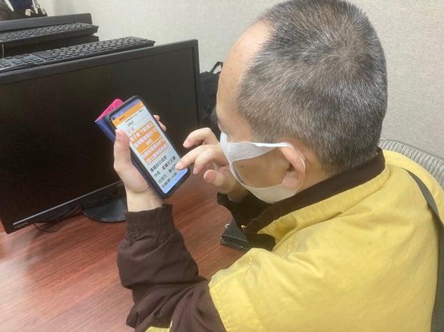 使用手機操作視障隨身聽APP,找尋想要閱讀的書籍。